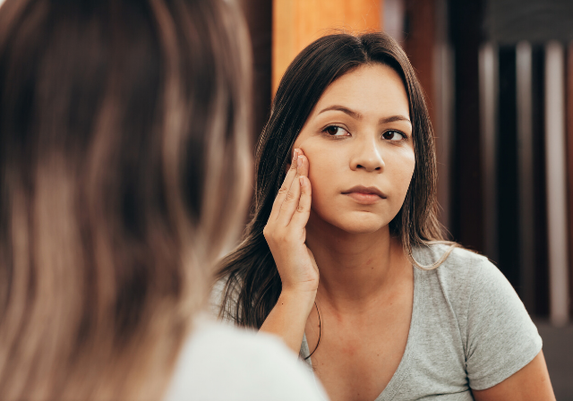 Woman checking her post-iso skin in the mirror and needing a non-invasive skin treatment